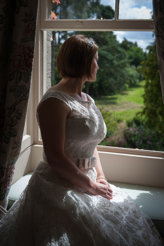 Bride looking out of a window