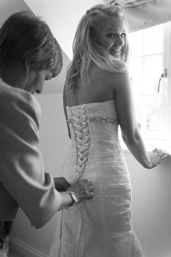 Brides mother fastening the brides dress
